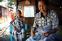 An elderly woman repairing fishing nets whilst being watched by her husband, Lae Lae, Makassar, Sulawesi, Indonesia.