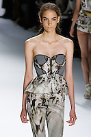 Zuzanna Bijoch walks runway in a Charcoal super pique peplum corset with psychedelic bust detail, and White psychedelic printed stretch cotton legging, by Vera Wang, for the Vera Wang Spring 2012 collection, during Mercedes-Benz Fashion Week Spring 2012.