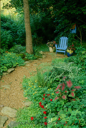 Blue adirondack chair with matching birdhouse sits at the end of the garden trail-- a private reward
