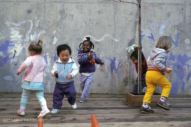 Berkeley CA Children engaging in wild, associative play and running at day care, ages one and a half to two years