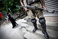 Kashmiri Muslims walk by pass of paramilitary as they guard the access to downtown Srinagar declared under curfew. Currently, 750,000 to 800,000 (the exact number remains unknown and disputed) Indian military and paramilitary are deployed in Kashmir, making this one of the world's most militarized regions. The Indian government has passed security legislation giving military and police forces special powers to suppress insurgency and maintain a fortified presence in the region, triggering off all types of human right violations including  systematical rapes, abductions, executions and disappearances. Srinagar, Indian administrated Kashmir.