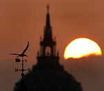 A weather vain points north south as the sun rising from the east silhouette city hall from the west in San Francisco, California.