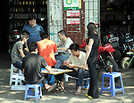 Asia, China, Chongqing. Teens playing card games on the sidewalks.