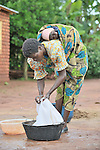 Her baby on her back, a woman does laundry in Dundube Kadambo, in northern Malawi.