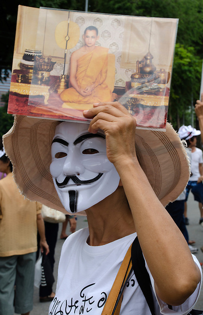 BANGKOK, July 14: White-Mask protestor shows a photo of ther King as a monk when anti-government protestors supporting the white-mask movement against corruption in the Yingluck Shinawatra government gathered at Lumpini Park on the second anniversary of the Yingluck administration to protest the blatant corruption in government policy and practice. July 14, 2013, Bangkok, Thailand