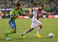 Michael Harrington, right, of the Portland Timbers dribbles the ball in front of Brad Evans of the Seattle Sounders FC during play at CenturyLink Field in Seattle Saturday August, 3, 2013. The Sounder won the match 1-0.