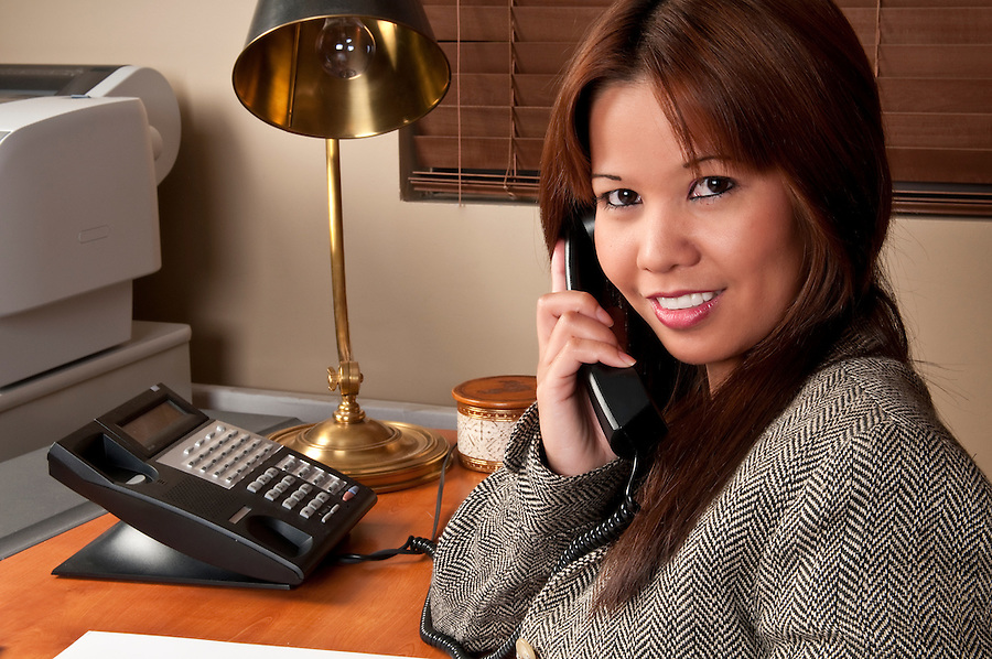 Young executive woman in small business talking in the phone.