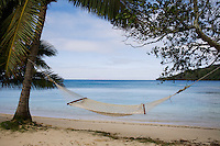 A hammock is strung between two trees on the sandy beach