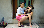 Eileen Peralta and her 12-year old daughter Erin, who has autism, sit on the step of their home in the Malate neighborhood of Manila. They are members of Kaisahan ng Magulang at Anak na Maykapansanan (Kaisaka), a mothers' group that carries out community based rehabilitation with families which have members with disabilities.