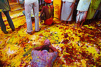 A man is laying on the floor full of mud-of-color, in order to show respect to the Gods.