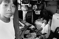 Philippines. National Capital Region. Manila. Paradise village. A mother and her young daughter inside their wooden hut. Paradise village has a population of 15'000 people and is a part of Barangay Tonsuya situated on Lettre Road in Malabon. Manila is part of the National Capital Region (NCR) on Luzon island. Manila is the capital of the Philippines and one of the sixteen cities that comprise Metro Manila. Metro Manila is the most populous metropolitan area in the Philippines. © 1999 Didier Ruef