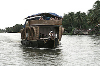 Foreign tourists on a houseboat in the backwaters of Alleppey, Kerala, India.