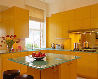 The kitchen is designed around an island unit with a glass work-surface surrounded by cupboards with yellow spray-painted panels