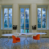 A pair of striking orange chairs and an oblong table by Vico Magistretti furnish this terrazzo-floored room