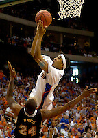 JACKSONVILLE, FL. 3/18/06-Florida's Corey Brewer goes over Wisconsin-Milwaukee's Boo Davis as he flies to the basket during first half action of the second round of the NCAA tournament at Jacksonville Veterans Memorial Arena. Brewer scored a team high 23 points. Brewer and Davis both took a hard fall on the play and were down for several minutes. The Gators beat the Panthers 82-60 to advance to the Sweet Sixteen in Minneapolis. COLIN HACKLEY PHOTO
