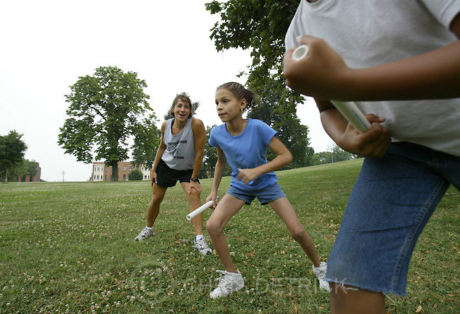 BALTIMORE, MD.--JULY 22, 2004--  Patterson Park track team members Shamerrah Parrison, 9, center in blue shirt,  ?nd Aaron Beace, 10, far right, wait for coach Lisa Bahl-Long, far left, to give the signal to start a relay race Thursday evening at Patterson Park.  This free program is eight weeks long and meets once a week during the summer. The Patterson Park team began an eight-week program designed to enhance participation, teamwork, fitness and fun. The program covers the basics of running, including streatching, preparation, diet and racing. Restrictions?? DIGITAL IMAGE #816G4122 BALTIMORE SUN STAFF PHOTO BY CHRIS DETRICK        No Mags, No Sales, No Internet, No TV