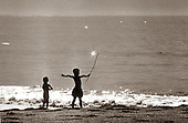 Young girl watches as small boy calls before him..the stars and sea on Christmas Eve. photo by jane therese