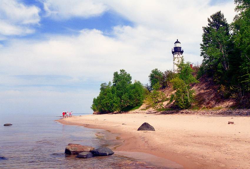 A FAMILY HIKES DOWN THE BEACH NEAR THE AU SABLE LIGHTHOUSE IN PICTURED ROCKS NATIONAL LAKESHORE NEAR GRAND MARAIS MICHIGAN.