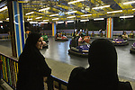 "Iraqi women from Baghdad watch as their family members ride the bumper cars at the ""Dream City"" amusement park in Duhok, Iraq. Although international tourism is almost non-existent, Kurdistan is a major destination for Iraqis seeking to escape the violence that has plagued the country follwing the US invasion in 2003...Stability and security prevail in postwar Iraqi Kurdistan as Iraqi tourists, many of them from Baghdad, flock to the northern cities and their amusement parks and national parks to escape violence and sectarian strife in the central and southern regions of the country."