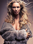 Beauty portrait of a woman with flying long blond hair wearing a fur coat with open decollete