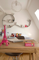 This attic bedroom is furnished with a desk and a Ron Arad 'Bookworm' bookshelf