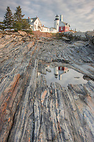 Pemaquid Point Lighthouse and its reflection in a tidal pool , looking up the slope of metamorphic rock formations , Bristol , Maine .