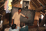 Marsh Arabs. Southern Iraq. Circa 1985. Marsh Arab children in school building. Traditional reed constructed building. Portrait of Saddam Hussein hanging from wall. Haur al Mamar or Haur al-Hamar marsh collectively known now as Hammar marshes Irag 1984