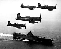 F4U's (Corsairs) returning from a combat mission over North Korea circle the USS Boxer as they wait for planes in the next strike to be launched from her flight deck - a helicopter hovers above the ship.  September 4, 1951. (Navy)<br /> NARA FILE #:  080-G-433002<br /> WAR &amp; CONFLICT BOOK #:  1414