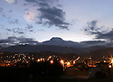 Volcano Cayambe seen at sunrise from a window in the village of Cayambe.