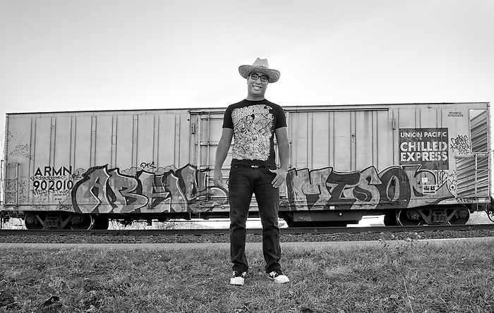 A young Hispanic man standing in front of a Box Car with Graffiti
