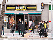 Pedestrians waiting to cross the street in front of a popular cafe franchise, Doutor.