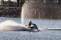 Water spray fills the air behind a personal watercraft, commonly called a Jet Ski, at San Leandro Marina Park along San Francisco Bay, California.
