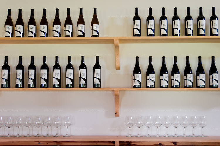 Wines and glasses are displayed on shelves behind the bar at Hume Vineyards.