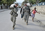 With help from U.S. soldiers, women take home food they received from the World Food Program during a massive distribution in Port-au-Prince, Haiti, less than three weeks after the January 12 earthquake that ravaged the Caribbean nation.