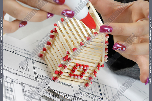 Young attractive businesswoman building a house from matches in her office Realtor Real estate agency Construction industry Home renovation Architectural design concept