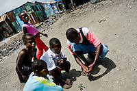 Haitian children play marbles in the slum of Cité Soleil, Port-au-Prince, Haiti, 24 July 2008. Cité Soleil is considered one of the worst slums in the Americas, most of its 300.000 residents live in extreme poverty. Children and single mothers predominate in the population. Social and living conditions in the slum are a human tragedy. There is no running water, no sewers and no electricity. Public services virtually do not exist - there are no stores, no hospitals or schools, no urban infrastructure. In spite of this fact, a rent must be payed even in all shacks made from rusty metal sheets. Infectious diseases are widely spread as garbage disposal does not exist in Cité Soleil. Violence is common, armed gangs operate throughout the slum.