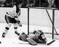 Seals Reggie Leach over Detroit Red Wings goalie Dennis DeJordy. (1974 photo/Ron Riesterer)