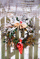 Holiday Wreath in winter snow and ice, hanging on gate of picket fence, exterior house home decorations for Christmas in December