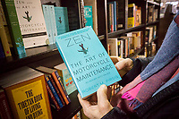 """A reader holds a copy  of """"Zen and the Art of Motorcycle Maintenance: An Inquiry into Values"""" by Robert M. Pirsig in a bookstore in New York on Tuesday, April 25, 2017. Pirsig, the author of the book with a cult following, died in Maine on Monday at the age of 88. (© Richard B. Levine)"""