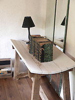 An unusual curved trestle table treated in a suble lime-wash finish can be found in a corner of the living room
