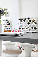 The kitchen/dining area features white modular wine racks and dimpled plastic stools complementing a grey table