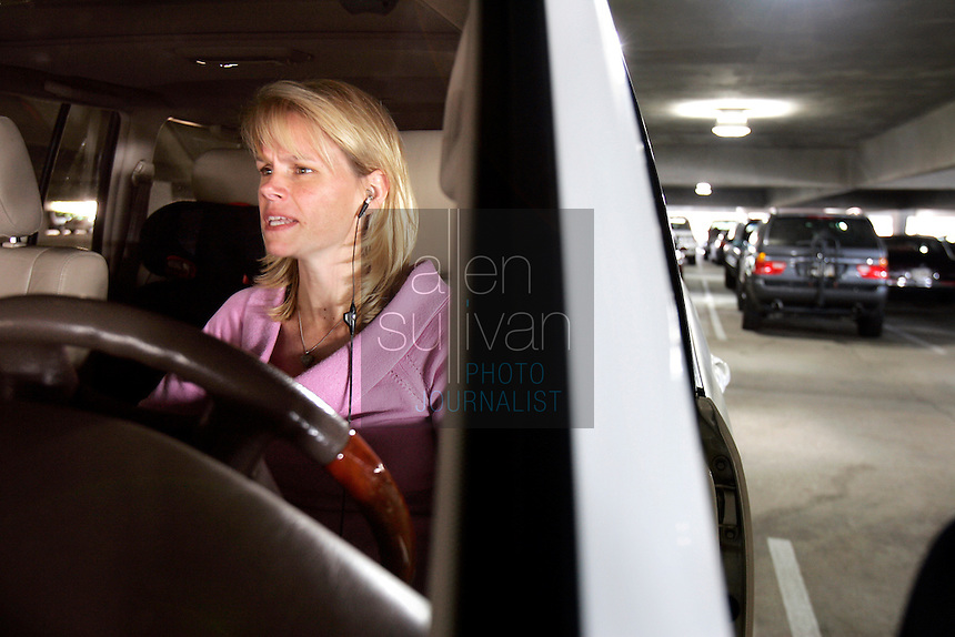 Sports agent Molly Fletcher speaks to a client by cell phone before heading up to her office at Career Sports and Entertainment on Wednesday morning, March 22, 2006. Fletcher must juggle a busy family life with her more than full-time job representing several top sports personalities.<br />
