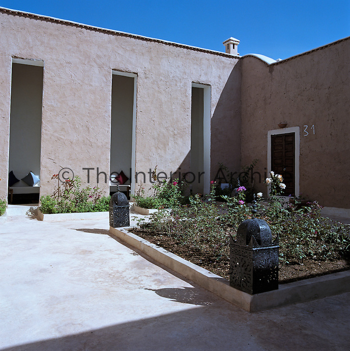 Tall narrow slits in the walls of this adobe-clad courtyard allow restricted light into one of the shady sitting areas