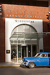 Havana, Cuba; a blue, classic 1954 Chevy parked on the street in front of the modern wing of the Hotel Parque Central in Havana