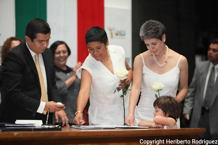Janice Jeanette Alva Vázquez (C) and Emma Estrellita Lauria Viilanueva (R) put their fingerprints on their marriage act as the civil judge Hegel Cortes looks on while becoming the first couple in getting married during a civil ceremony at the Mexico City's City Hall on March 11, 2010. For the first time in Mexico the gay marriages are being legalize although the Catholic church and the Felipe Calderon's government are opposing to the gay rights.  Photo by Heriberto Rodriguez