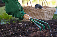 Photo of a gardener's gloved hand cultivating the soil.