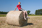 Teenager Boy Sitting on Hay Bale