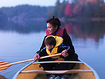Mother with a three year old boy learning to paddle a canoe, fall nature scenery. Kilarney, Ontario, Canada.