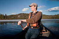 Writer Conor Mihell paddles a canoe solo on Marina Lake at Lady Evelyn-Smoothwater Provincial Park in Ontario Canada.