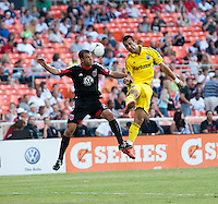 Daniel Woolard (21) of D.C. United goes up for a header with Justin Meram (9) of the Columbus Crew during the game at RFK Stadium in Washington, DC.  D.C. United defeated the Columbus Crew, 1-0.